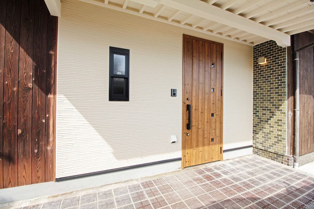 玄関は観音開きから開き戸に変更し、壁もサイディングに張り替えました。玄関扉にはLIXILジエスタ2を使用しました。また、外壁の焼杉板も一部張り替えました。