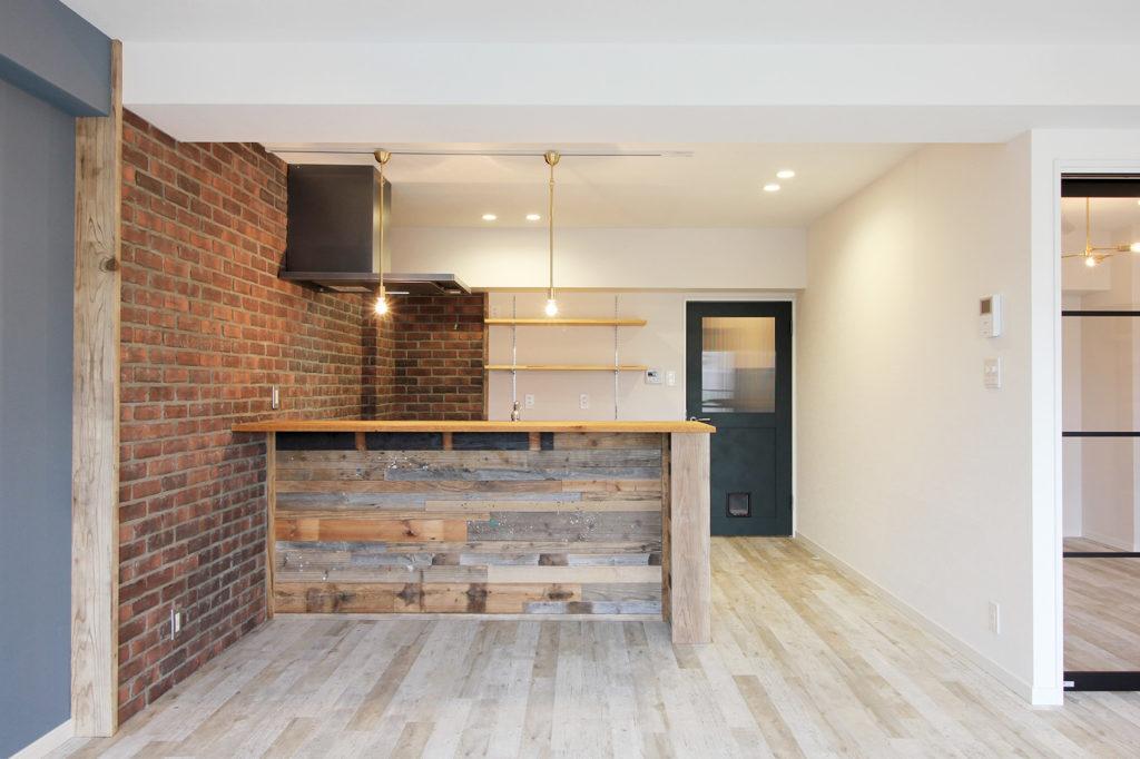 キッチンカウンターには足場板などに使用された古材を張りました。フード側にはブルックリン風にレンガを貼っていきました。
