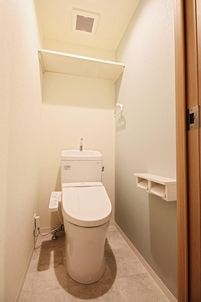 トイレは、TOTOの手洗い付便器を使用しています。側面にはアクセントとしてグリーンの壁紙を使用しました。